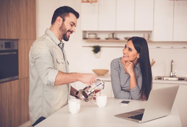 De mens schenkt thee terwijl zijn vrouw hem bekijkt.