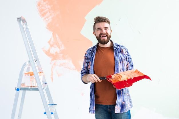 De mens schildert de muur met verf