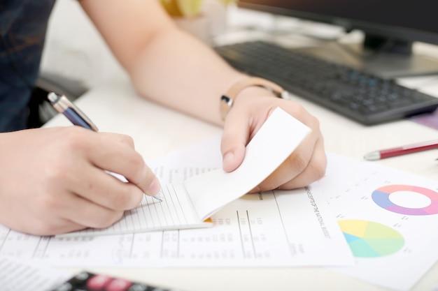 De mens schrijft het werk op blocnote met in hand pen.