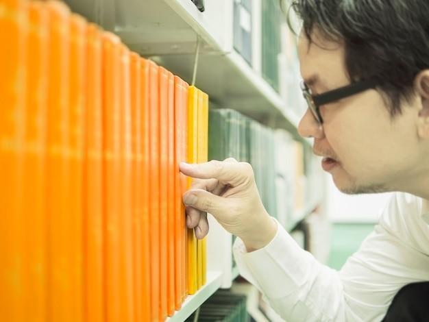 De mens selecteert het boek van boekenplank in een bibliotheek