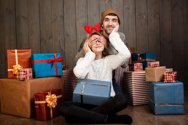 De mens sluit de ogen van zijn vriendin met overhandigt houten muur