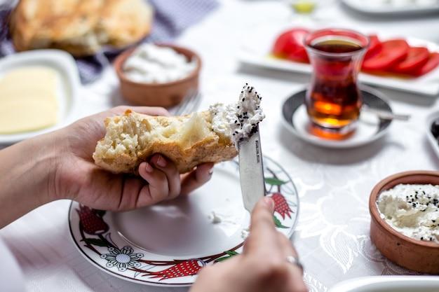 De mens smeert shor vergist melkproduct op het brood zijaanzicht