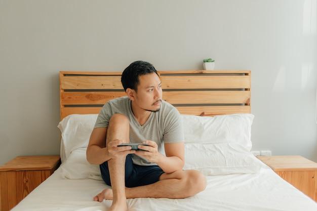 De mens speelt mobiel spel met zijn smartphone op het bed.