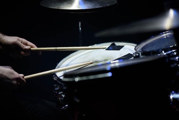 De mens speelt muzikaal slaginstrument met stokkenclose-up, een muzikaal concept met de werkende trommel, mooie verlichting op het stadium