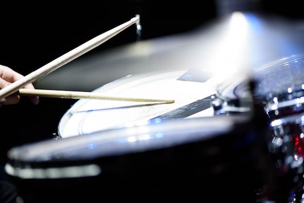 De mens speelt muzikaal slaginstrument met stokkenclose-up op een zwarte achtergrond, een muzikaal concept met de werkende trommel, mooie verlichting op het stadium