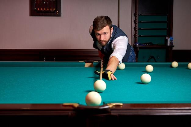 De mens speelt snooker, het jonge mannetje streeft ernaar om de snookerbal te schieten. knappe jongen houdt handen op snookertafel. biljart