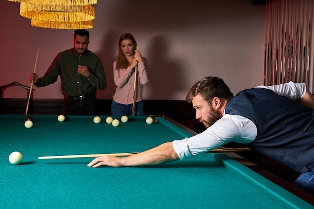 De mens speelt snooker, hij streeft ernaar om de snookerbal te schieten. knappe jongen houdt handen op snookertafel. biljart