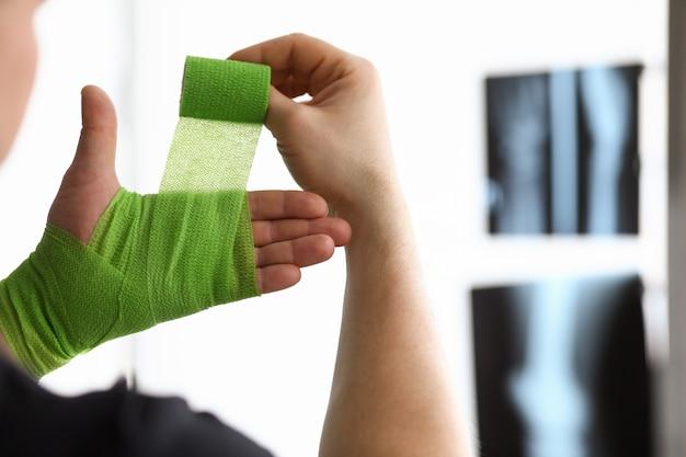 De mens spoelt zijn hand met verband op een röntgenfoto terug