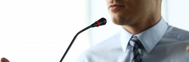 De mens spreekt thuis vooraan microfoon in conferentie