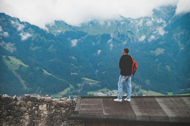 De mens staat op het dak en kijkt naar bergen