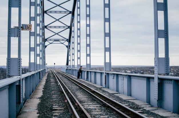 De mens staat verveeld op rails van een oude spoorbrug, helaas wachtend op een vergadering. industrieel landschap. grote ijzeren brug op een bewolkte dag. het concept van scheiding, ontmoeting, depressie. kopieer ruimte