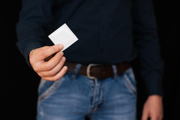 De mens steekt een condoom uit voor bescherming