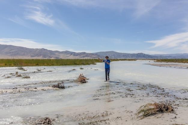 De mens steekt te voet een witte bergrivier over. altai, mongolië.