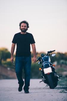 De mens stelt dichtbij zijn motorfiets bij zonsondergang