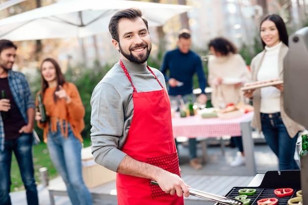 De mens stelt op de camera tijdens het koken van voedsel op de grill.