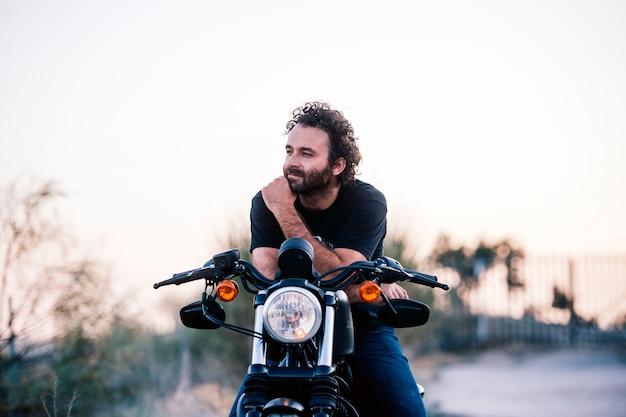 De mens stelt op zijn motorfiets bij sunsett