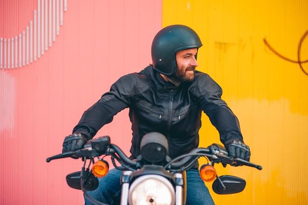 De mens stelt op zijn motorfiets bij zonsondergang