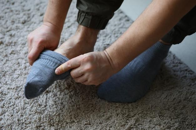 De mens thuis in ochtend zet grijze sokken op zijn been