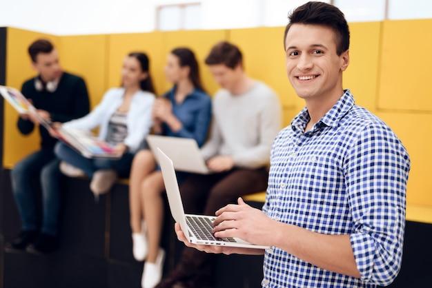 De mens typt op laptop in creatief bureau met collega's.