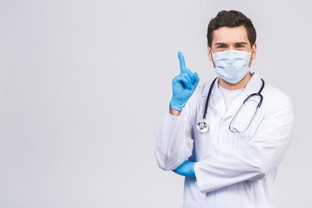 De mens van de arts in medische geïsoleerde het maskerhandschoenen van het toga steriele gezicht. epidemie pandemisch coronavirus 2019-ncov sars covid-19 griepvirus. wijsvinger opzij.