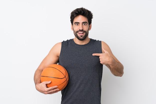 De mens van de basketbalspeler met baard over geïsoleerde witte muur met verrassingsgelaatsuitdrukking