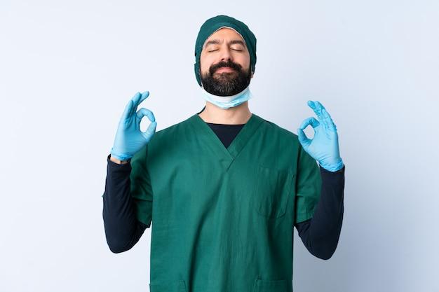 De mens van de chirurg in groen uniform over geïsoleerde muur in zen stelt
