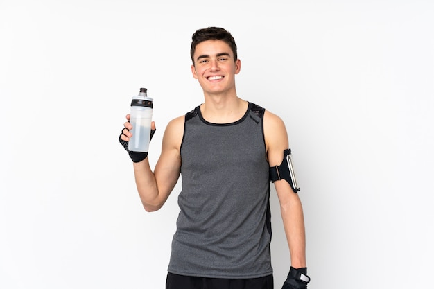 De mens van de tienersport over geïsoleerde witte muur met de fles van het sportenwater
