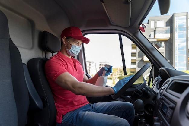 De mens van de zijaanzichtlevering met masker schoonmakende auto