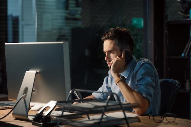 De mens van het concentreren in bureau dat telefoongesprek heeft