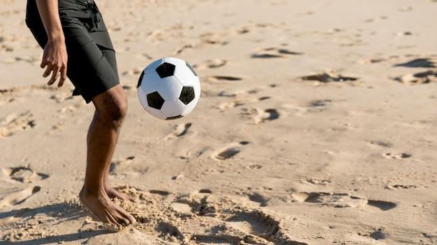 De mens van het gewas het schoppen bal op zandig strand