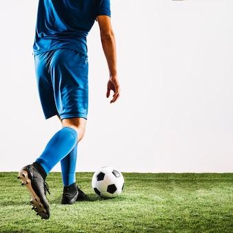 De mens van het gewas in blauwe eenvormige het schoppen bal