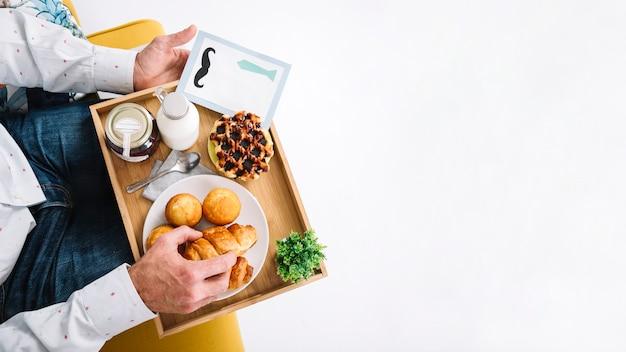 De mens van het gewas met dienblad dat ontbijt heeft