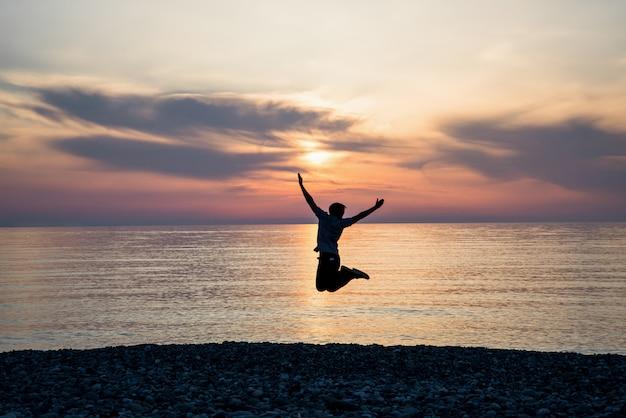 De mens van het silhouetgeluk op het zonsopgangstrand