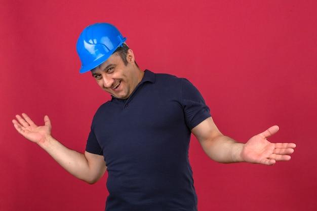 De mens van middelbare leeftijd die poloshirt en het glimlachen van de veiligheidshelm dragen strekt zijn handen naar voren uit alsof hij iemand over geïsoleerde roze muur wil ontmoeten