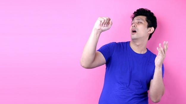 De mens van portret het knappe azië luid zingen terwijl status op roze achtergrond in studio