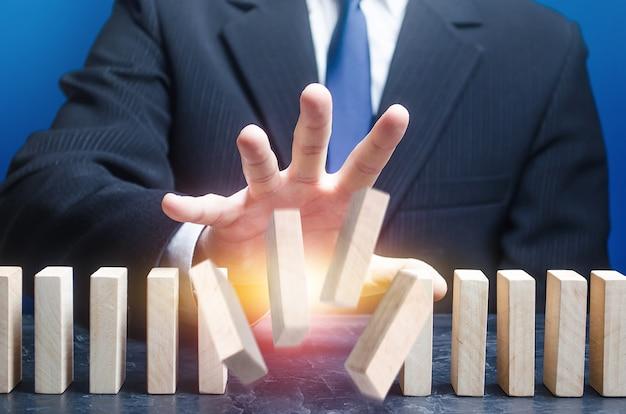 De mens vernietigt de volgorde van de staande domino-rij.