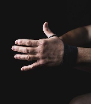 De mens verpakt zijn handen in zwart textielverband