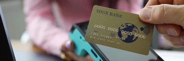 De mens verricht geldloze betaling en houdt de gouden kaart in de hand