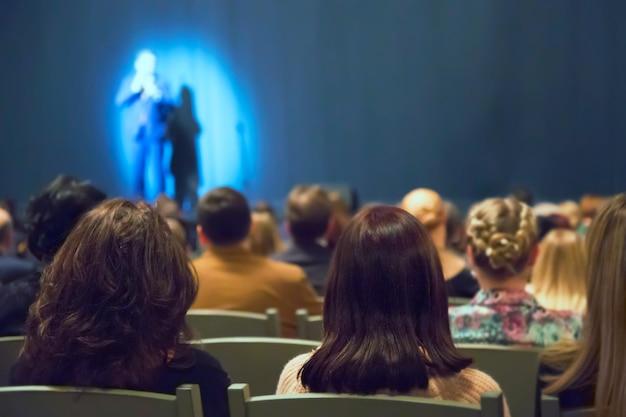 De mens verschijnt met veel mensen op het podium in het theater
