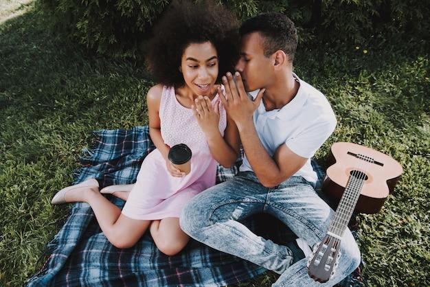 De mens vertelt iets aan zijn vriendin. zonnige zomerdag