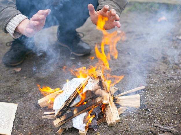 De mens verwarmt zichzelf bij het vuur, kampvuurvuur.