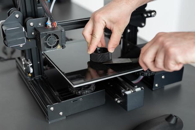 De mens verwijdert het voltooide onderdeel van een 3d-printer