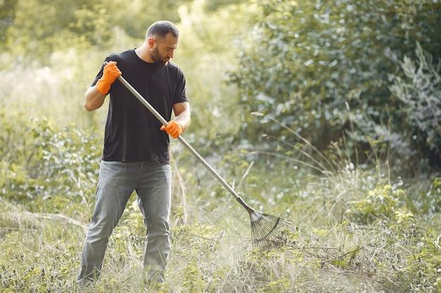 De mens verzamelt bladeren en maakt het park schoon
