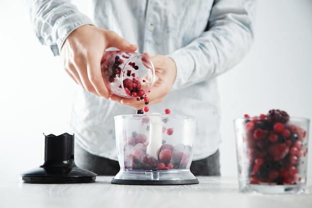 De mens voegt bevroren bessen toe aan de gerichte blenderpot voordat hij een smakelijke smoothiedrank maakt om op te frissen in de zomer. ongericht glas met bevroren bessen vooraan dichtbij