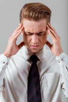 De mens voelt zich moe en raakt zijn gezicht aan.