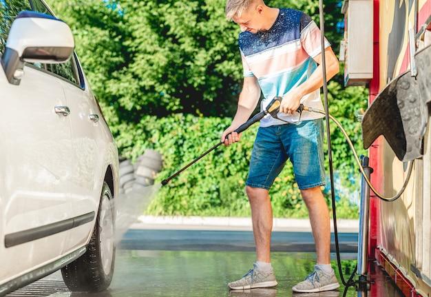 De mens wast auto met water onder hoge druk