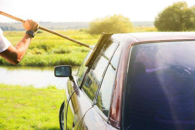 De mens wast oude auto. buiten reinigen van het voertuig. natte dweil.