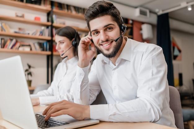 De mens werkt als callcenterondersteuningsexploitant met hoofdtelefoon het typen op laptop