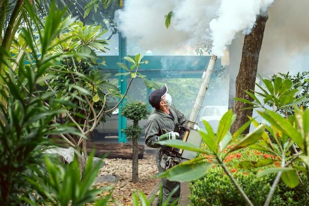 De mens werkt beslaan om muggen te elimineren en verspreiding van knokkelkoorts te voorkomen
