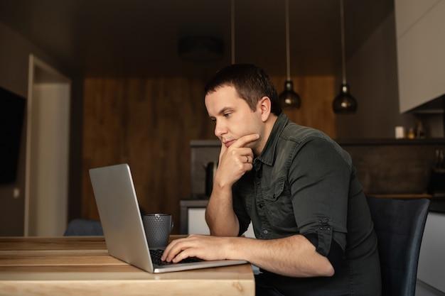 De mens werkt binnen aan laptop, bij het bureau in de keukenruimte. werk vanuit huis